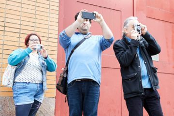 Three patients taking photos outside a building