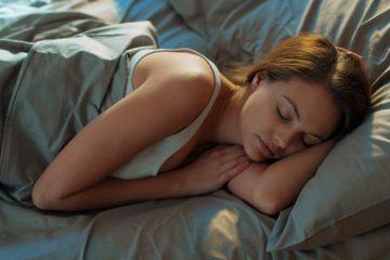 A woman sleeping on green sheets