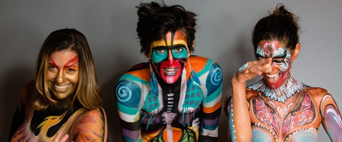 A portrait of three women in face and body paint