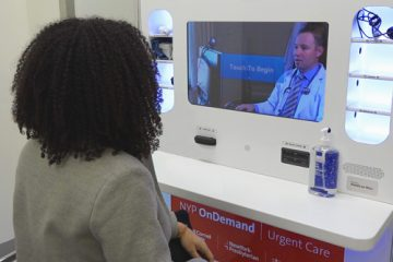 A woman using a telemedicine kiosk to speak with a healthcare provider