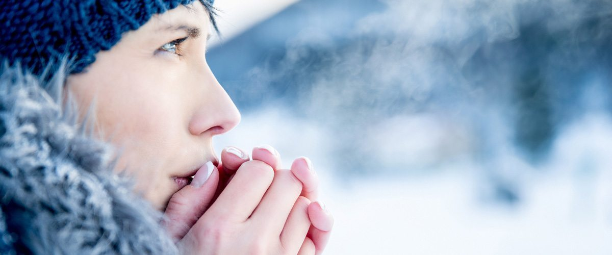 A chilly woman breathing warm air into her hands