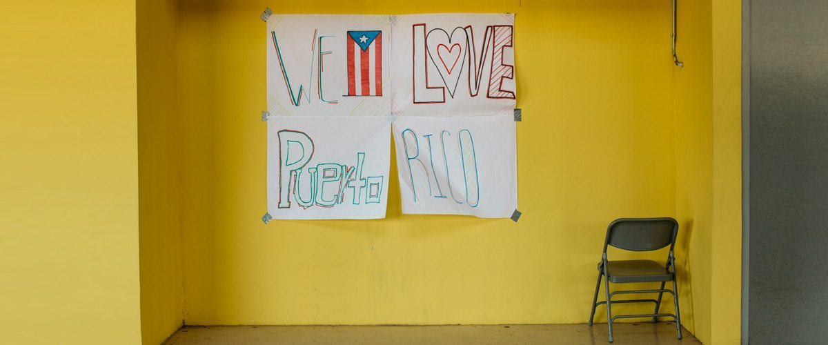 """Yellow wall with a hand-written sign saying """"We Love Puerto Rico"""""""