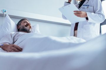 A man listening to a healthcare provider from his hospital bed