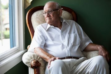 An elderly man looking out a window