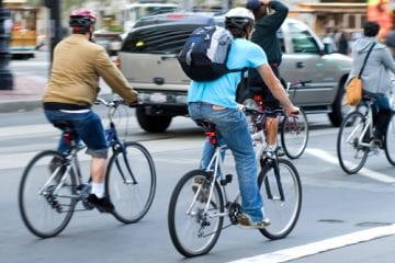 People cycling through city street with and without bike helmets.