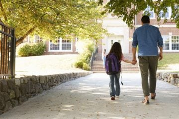 A father and daughter walking to school