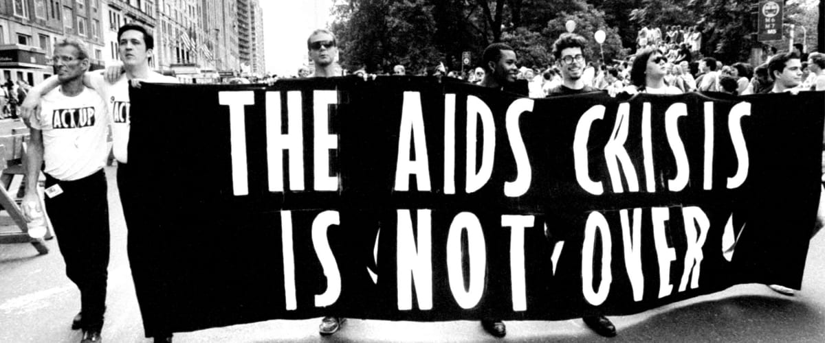 """Marchers with a banner that says """"The AIDS Crisis Is Not Over"""""""