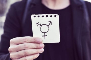 A person holding a piece of paper with a transgender sign on it