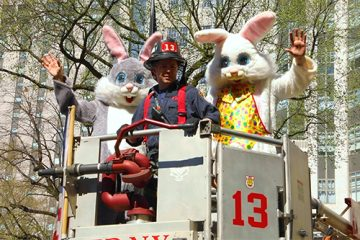 Two costumed bunny rabbits and a firefighter atop a fire truck