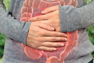 A women clutching her abdomen which depicts an illustration of the human intestines