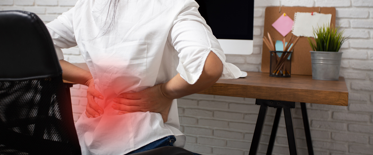 Photo of woman with back pain from too much sitting.