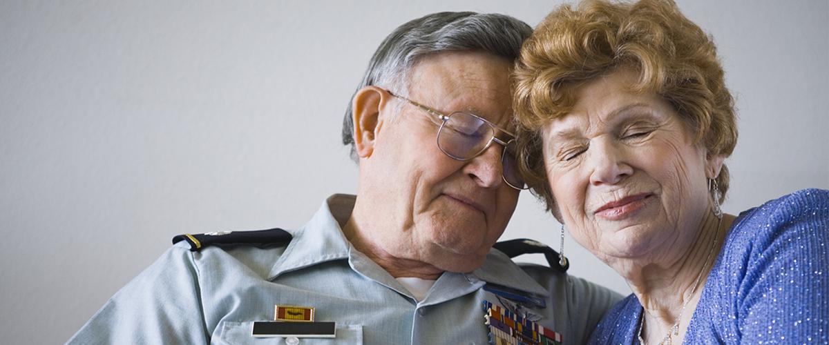 Elderly war veteran with wife.