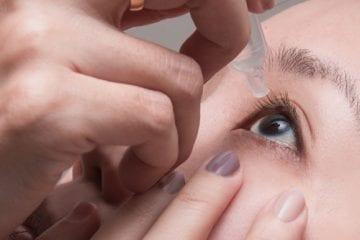 Photo of woman adding eye drops to eye