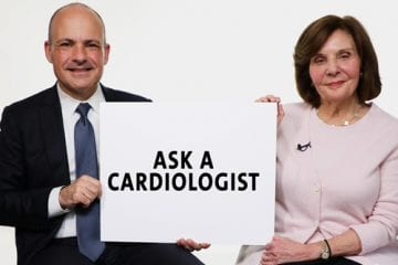 Dr. Emmanuel Moustakakis and Dr. Elsa-Grace Giardina hold a sign for a video debunking heart health myths