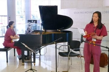 A woman in pink scrubs sings while another woman plays a piano