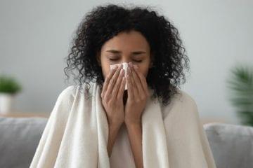woman blowing nose from seasonal allergies
