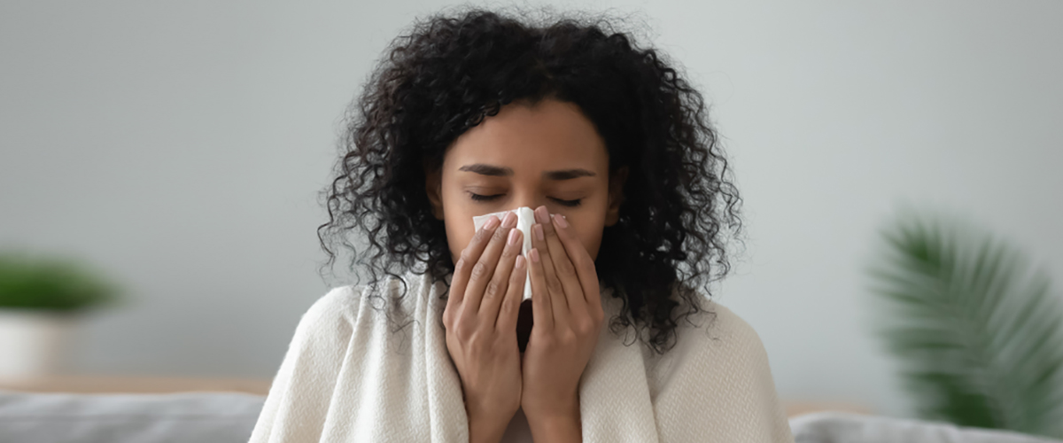 woman blowing her nose from seasonal allergies