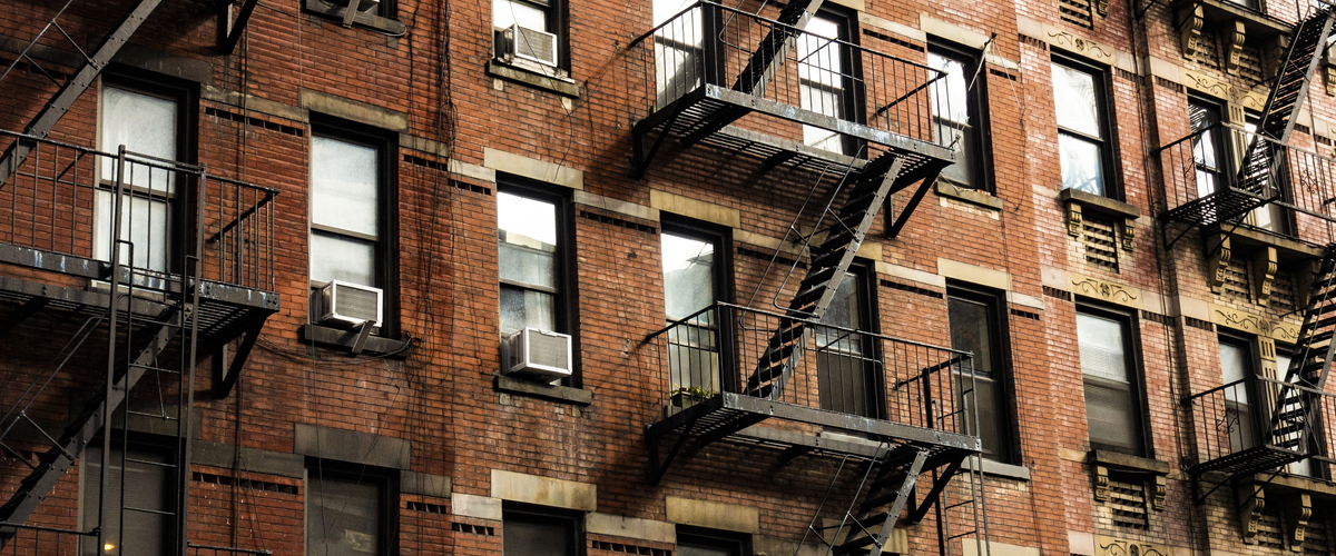 Exterior of apartment building with lots of windows and fire escapes.