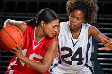 Two female basketball players playing basketball