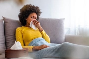 Woman on the couch sick with either flu or COVID-19.