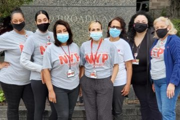 Community Health Workers stand with NYP shirts and surgical face masks