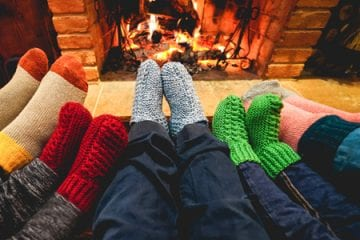 family celebrating the holidays safely in front a fireplace