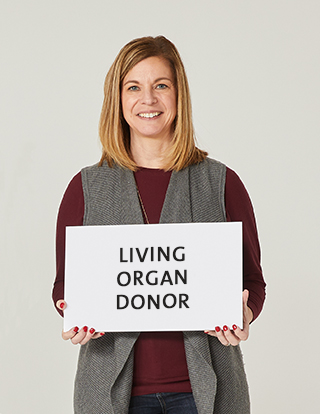 """Living organ donor Tracy Kent holding a sign that says """"living organ donor."""""""