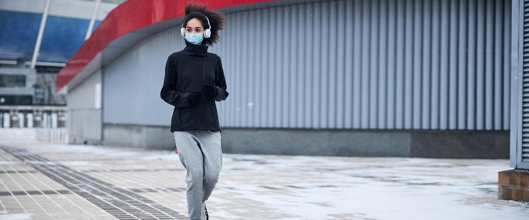 Woman running outdoors, wearing a mask.