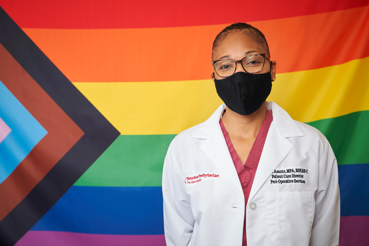 Healthcare worker standing in front of Pride Progress flag to celebrate Pride Month.