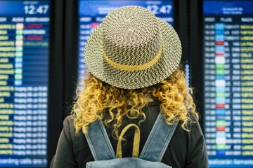 Woman looks at flight board while traveling during COVID